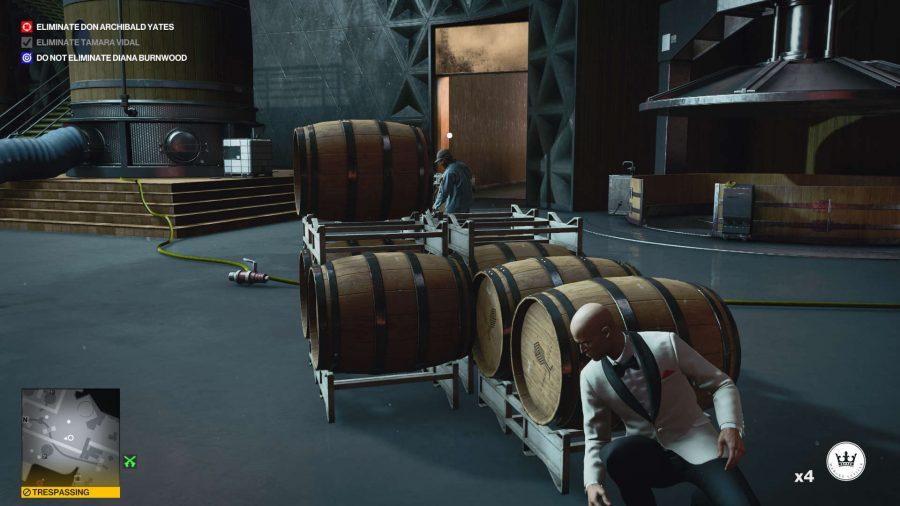Agent 47 versteckt sich in einer Brennerei, während er unterwegs ist, um einen der Tastaturcodes in Hitman 3s Mendoza-Mission freizuschalten.