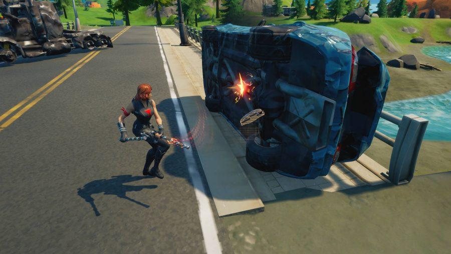 Der Spieler hackt ein umgedrehtes Auto weg, um mechanische Teile für die Herstellung in Fortnite zu ernten.  Ein explodierter Lastwagen ist in der Nähe.